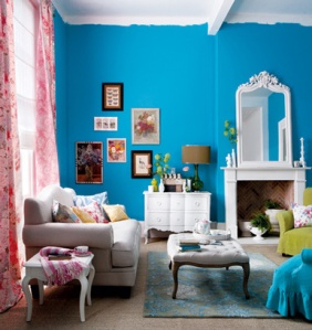 A turquoise wall with soft white furniture